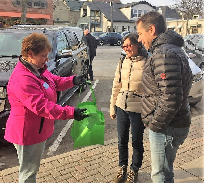 Plymouth City Commissioner Suzi Deal offers a selection of downtown business gift cards to a couple from Ann Arbor Friday afternoon.