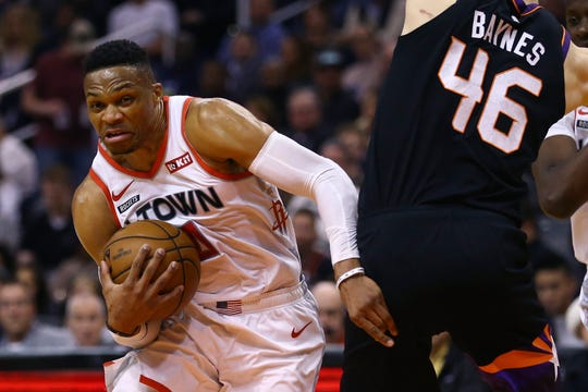 Houston Rockets guard Russell Westbrook, left, drives past Phoenix Suns center Aron Baynes (46) during the first half of an NBA basketball game Saturday, Dec. 21, 2019, in Phoenix. The Rockets defeated the Suns 139-125. (AP Photo/Ross D. Franklin)