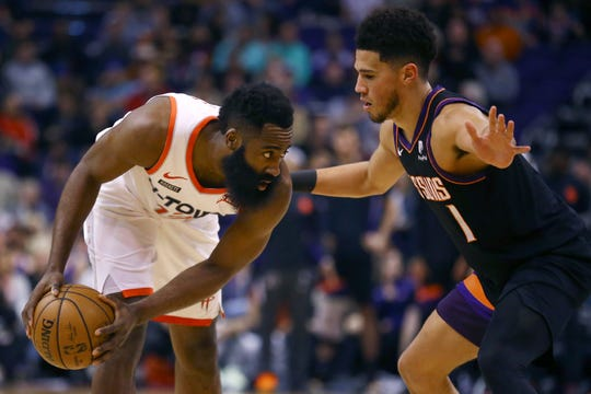 Houston Rockets guard James Harden, left, pauses with the ball as Phoenix Suns guard Devin Booker (1) defends during the first half of an NBA basketball game Saturday, Dec. 21, 2019, in Phoenix. The Rockets defeated the Suns 139-125. (AP Photo/Ross D. Franklin)
