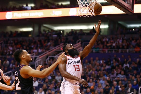 Houston Rockets guard James Harden (13) drives past Phoenix Suns forward Elie Okobo (2) to score during the first half of an NBA basketball game Saturday, Dec. 21, 2019, in Phoenix. (AP Photo/Ross D. Franklin)