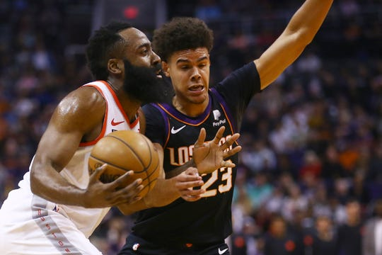 Houston Rockets guard James Harden, left, drives past Phoenix Suns forward Cameron Johnson (23) during the first half of an NBA basketball game Saturday, Dec. 21, 2019, in Phoenix. The Rockets defeated the Suns 139-125. (AP Photo/Ross D. Franklin)