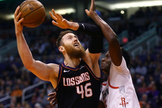 Phoenix Suns center Aron Baynes (46) goes up to shoot against Houston Rockets center Clint Capela, right, during the second half of an NBA basketball game Saturday, Dec. 21, 2019, in Phoenix. (AP Photo/Ross D. Franklin)