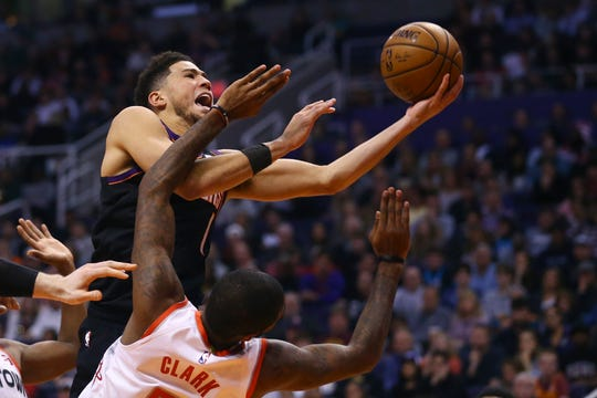 Phoenix Suns guard Devin Booker, top, is fouled as he goes up for a shot by Houston Rockets forward Gary Clark, bottom, during the second half of an NBA basketball game Saturday, Dec. 21, 2019, in Phoenix. (AP Photo/Ross D. Franklin)