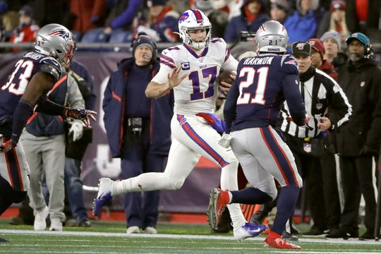 Buffalo Bills quarterback Josh Allen, center, runs with the ball as New England Patriots defenders Joejuan Williams, left, and Duron Harmon, right, give chase in the second half of an NFL football game, Saturday, Dec. 21, 2019, in Foxborough, Mass.