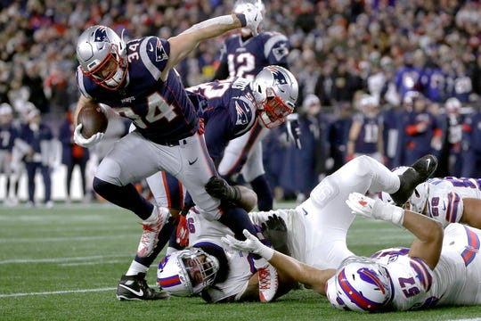 New England Patriots running back Rex Burkhead breaks loose from an attempted tackle to run for a touchdown against the Buffalo Bills in the second half of an NFL football game, Saturday, Dec. 21, 2019, in Foxborough, Mass.