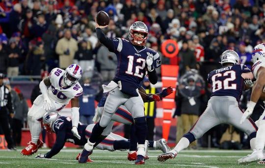 New England Patriots quarterback Tom Brady (12) throws as Buffalo Bills defensive end Shaq Lawson (90) rushes during the second quarter at Gillette Stadium.