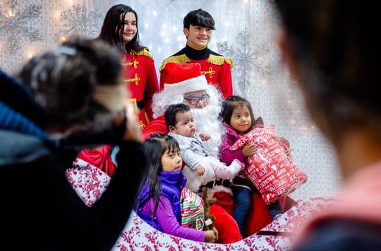 Children begin to get their photo taken with Santa Claus during the 2019 Cesar Chavez Futbol Academy winter toy drive on Dec. 20.