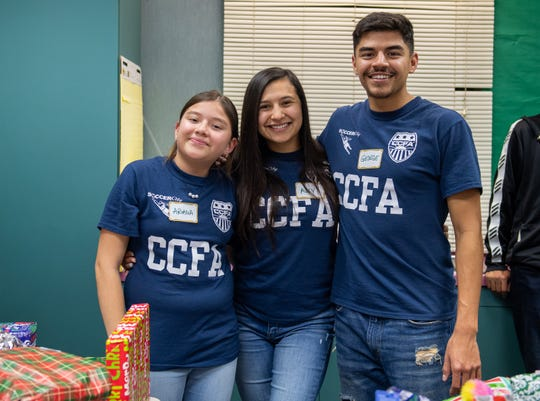 Three volunteers pose and smile for a photo during the 2019 Cesar Chavez Futbol Academy winter toy drive on Dec. 20.