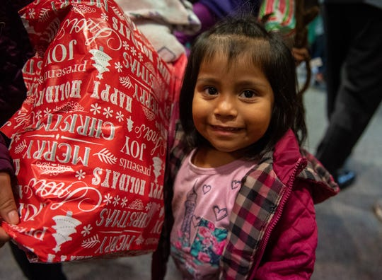 A young child smiles as she holds her gift during the 2019 Cesar Chavez Futbol Academy winter toy drive on Dec. 20.