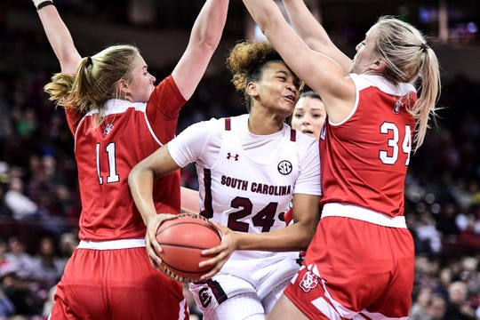 South Carolina guard LeLe Grissett (24) battles in the paint against South Dakota center Hannah Sjerven (34) and Monica Arens (11) during the first half of an NCAA college basketball game Sunday, Dec. 22, 2019, in Columbia, S.C.