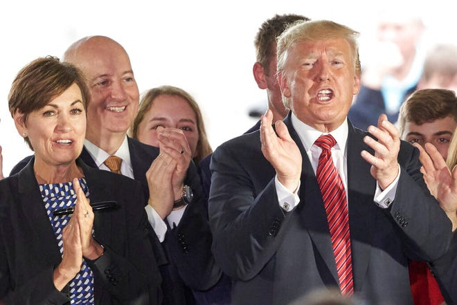 In this June 11, 2019 photo, President Donald Trump applauds next to Governors Pete Ricketts of Nebraska, second left, and Kim Reynolds of Iowa, left, in Council Bluffs, Iowa. An executive order by Trump giving states the right to refuse to take refugees is putting Republican governors in an uncomfortable position. They're caught between immigration hardliners who want to shut the door and others who believe helping refugees is a moral obligation.  (AP Photo/Nati Harnik)