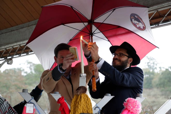 Mayor John Dailey and Rabbi Schnuer Zalman Oirechman work together to light the shamash, or service candle, on Chabad of Tallahassee's 9-foot menorah at Lake Ella Sunday, Dec. 22, 2019.