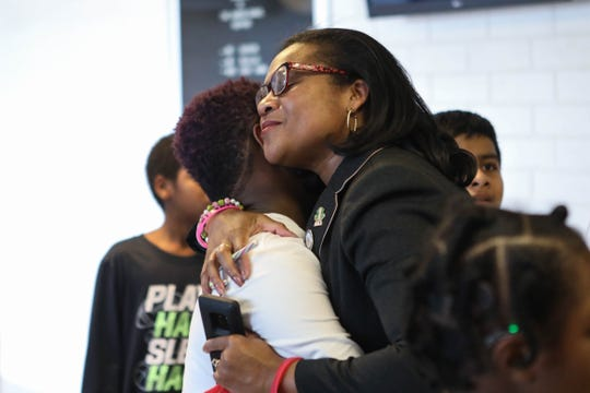 State Rep. Sherry Dorsey Walker gives a student a hug during a holiday event at Bayard School on Friday.