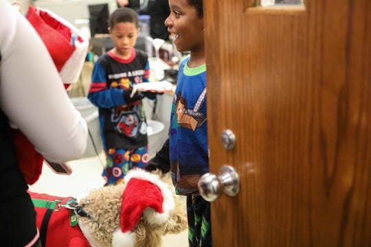 Bayard school students are excited to see Duke Ellington, a dog dressed as Santa, make his way into the nurses office with a group of volunteers handing out candy on Friday.