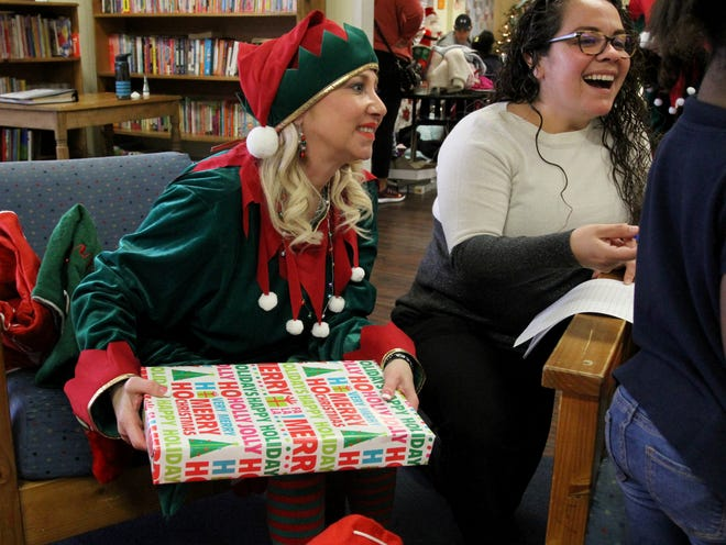 Delora King helps with giving out gift at the childrens home Friday, Dec. 20, 2019.