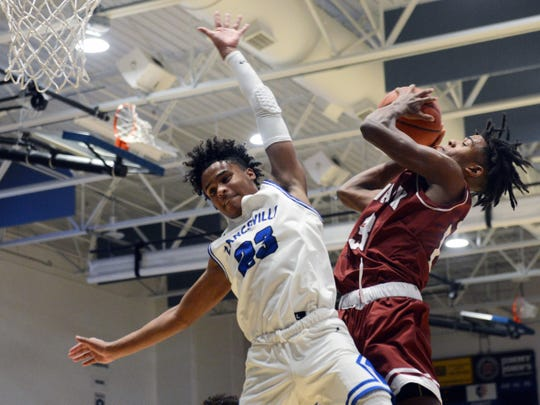 Bobby Crenshaw, of Newark, shoots over Zanesville's Greg Gibson during the second half of the Wildcats' 83-48 win on Saturday night at Winland Memorial Gymnasium.