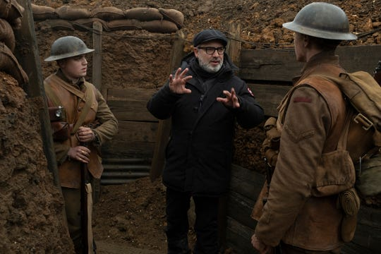 "Director Sam Mendes (center) goes over a trench scene with stars Dean-Charles Chapman and George MacKay on the set of ""1917."""