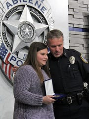 Kaitlyn Viola is hugged by Abilene police Chief Stan Standridge after he honored her for her role in saving two boys in chilled water Saturday in the Fairway Oaks neighborhood. Her father, Vince, also was recognized publicly in the rescue.