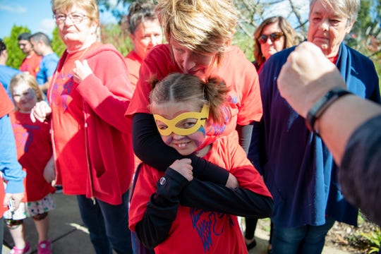 Lorrie Bentz hugs Charlie Buckley during the Battle Creek NephCure Walk at Leila Arboretum on October 6, 2019.