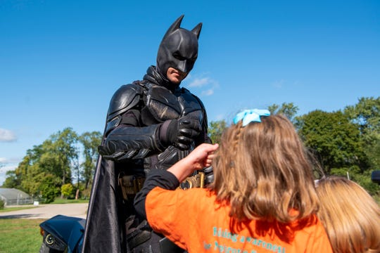 The Dark Knight of Michigan gives out a fist bump during the Battle Creek NephCure Walk at Leila Arboretum on Sunday, October 6, 2019.
