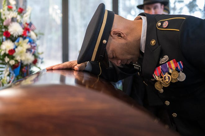 Sgt. Jose Burgos pauses for a moment at the casket of Vietnam veteran Peter Turnpu as several hundreds gather for a funeral Friday, Jan. 18, 2019 in Wrightstown, N.J.