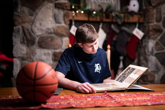 Junior Logan Bennett looks through a scrapbook in his Frankfort, Ohio, home  of Chillicothe Gazette paper clippings that highlighted his dad and fellow friends and teammates who played on the Adena basketball team in the 1970s and early 1980s.