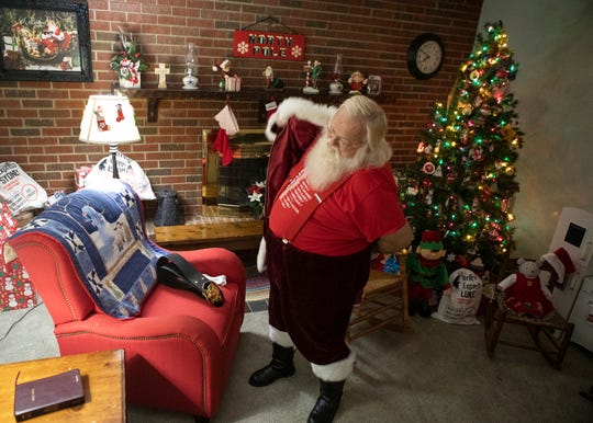 At 8 a.m. Nick Rose puts the finishing touches on his Santa Claus ensemble in his home in Chillicothe before going out to one of his numerous appearances.