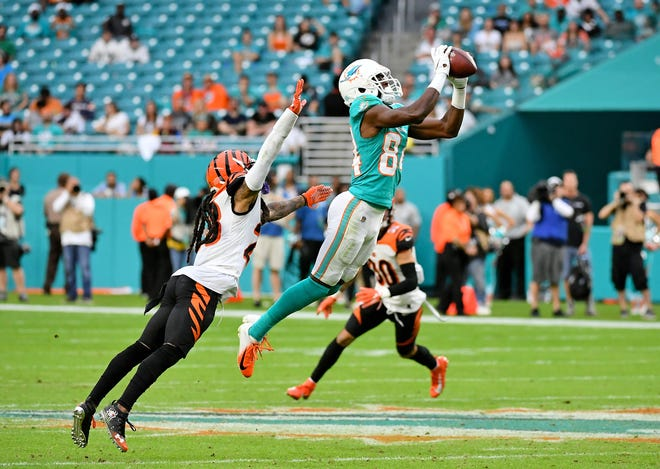 Dec 22, 2019; Miami Gardens, Florida, USA; Miami Dolphins wide receiver Isaiah Ford (84) makes a catch in front of Cincinnati Bengals cornerback B.W. Webb (23) during overtime at Hard Rock Stadium.