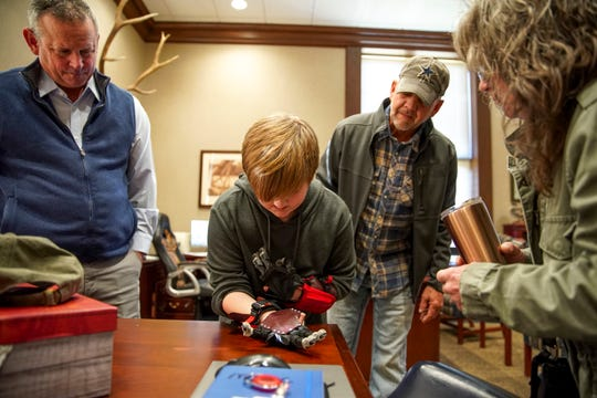 Gavin Sumner successfully releases the strap on his mechanical hand after having them fit for him at the Montgomery County Historic Courthouse in Clarksville, Tenn., on Monday, Dec. 23, 2019.