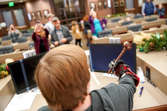 Gavin Sumner grips a gavel at the chairman seat where Montgomery County Mayor Jim Durrett would normally sit during county commission after being given his mechanical hands, which make gripping the gavel one handed possible at the Montgomery County Historic Courthouse in Clarksville, Tenn., on Monday, Dec. 23, 2019.