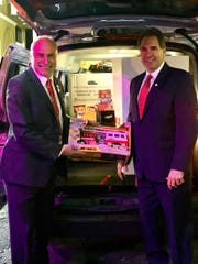 Mayor Owen Henry and Steve Mamakas, executive officer of the Mayor's Economic Development Office, are shown with the van full of toys.