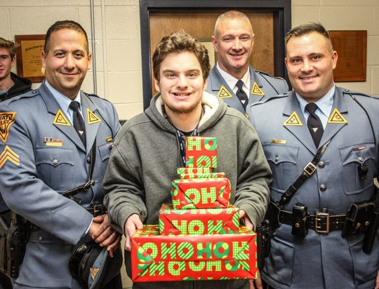 Theo Baransky of Milford is the recipient of this year's shower of gifts from the troopers of the Kingwood station. With him are (from left) Sgt. Scott Feldman, Lt. Sean O'Conner and Trooper Joe Seidler.
