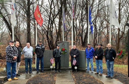 CMC Veterans with Father Thomas Ryan placed wreaths at the military mouments