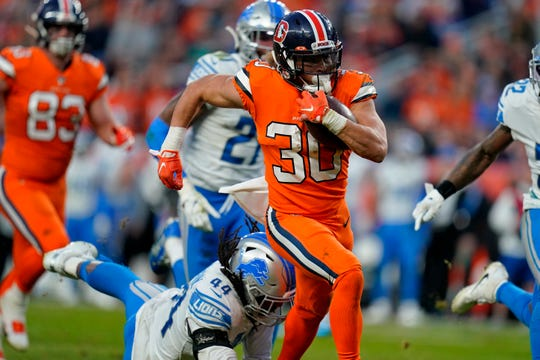 Broncos running back Phillip Lindsay breaks free from the grasp of Lions linebacker Jalen Reeves-Maybin for a touchdown during the second half of the Lions' 27-17 loss on Sunday, Dec. 22, 2019, in Denver.