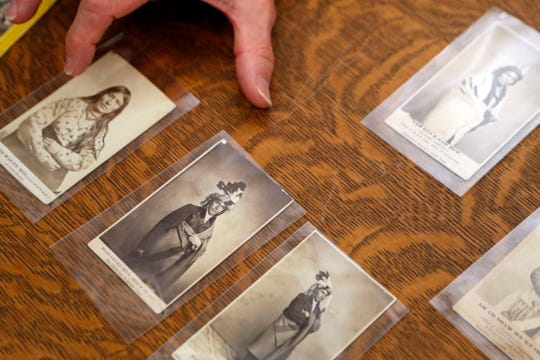 In this Thursday, Nov. 14, 2019 photo, University of Michigan William Clements Library Curator of Graphics, Clayton Lewis, shows examples of cartes de visite from the photographic collection acquired by the library in 2016 from Richard Pohrt Jr. in Ann Arbor, Mich. The trove, representing some 80 indigenous groups, includes photos from government-sponsored expeditions, stereographic and cartes de visites.