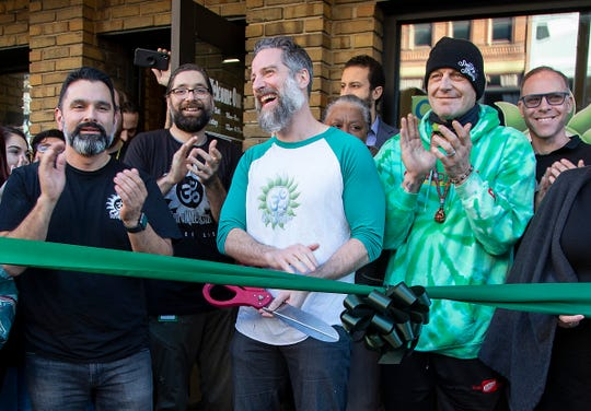 Om of Medicine on Main Street in Ann Arbor founders Mark Passerini (left hands up in air) and Keith Lambert celebrate a ribbon cutting with former Red Wing Darren McCarty as they can now legally sell recreational marijuana to its' patrons Monday, Dec. 23, 2019.