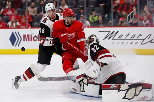 Coyotes goaltender Antti Raanta deflects a shot by Red Wings left wing Andreas Athanasiou during the third period of the Wings' 5-2 loss on Sunday, Dec. 22, 2019, at Little Caesars Arena.