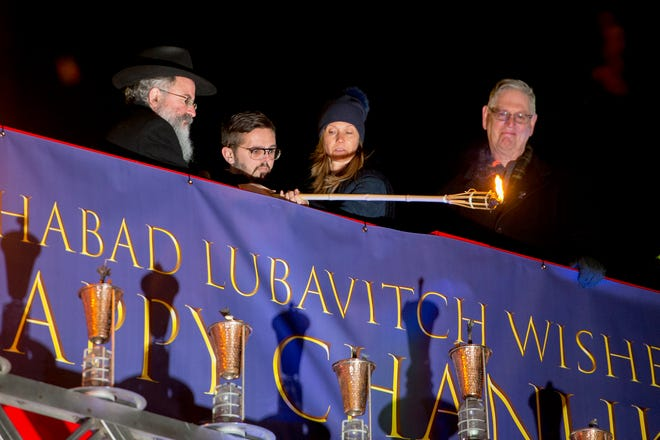 Rabbi Kasriel Shemtov of The Shul-Chabad Lubavitch in West Bloomfield and Nick Gilbert light the shamash candle of Detroit's menorah during Menorah in the D at Campus Martius in downtown Detroit on Sunday.