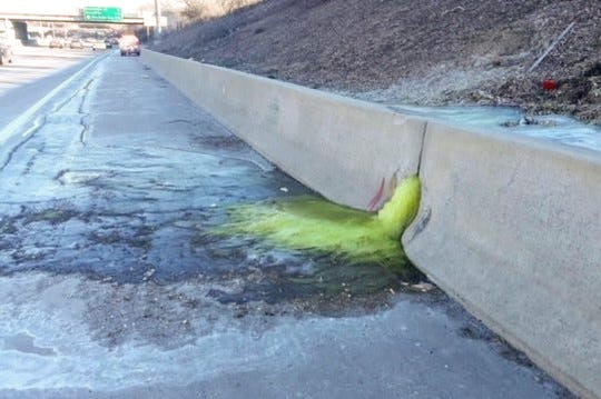 A greenish-yellow liquid flows through a retaining wall on I-696, triggering a lane closure Friday afternoon and haz-mat clean-up Friday night, Dec. 20, 2019.