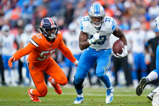 Detroit Lions running back Kerryon Johnson (33) runs as Denver Broncos outside linebacker Von Miller (58) pursues during the second half on Dec. 22, 2019, in Denver.