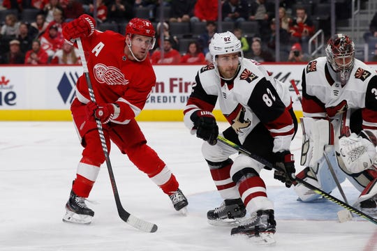Red Wings left wing Justin Abdelkader and Coyotes defenseman Jordan Oesterle play during the third period of the Wings' 5-2 loss on Sunday, Dec. 22, 2019, at Little Caesars Arena.
