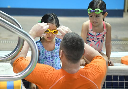 Arzoi Sandhu (left) gets her googles fixed by Goldfish Swim School instructor Donovan Cheridan in Canton.