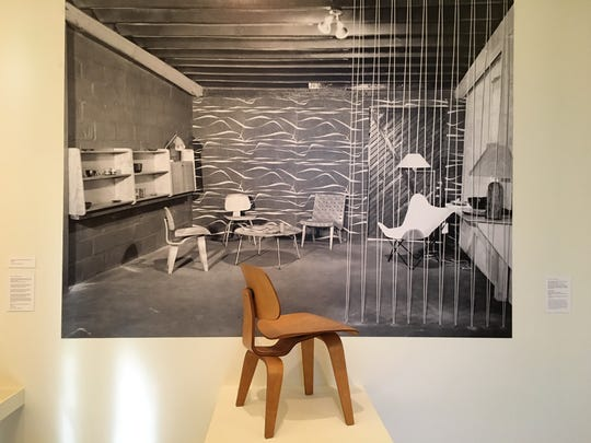 A Charles Eames LCW chair from 1946 at the Cranbrook Art Museum in front of a 1949 photo of the Adler-Schnee modern-furniture showroom in Detroit.