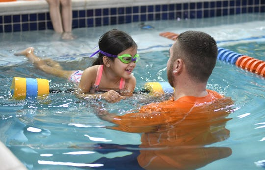 Goldfish Swim instructor Donovan Cheridan works on a swim lesson with Yeji Krupitzer, 3, of Canton,  at the Goldfish Swim School in Canton.
