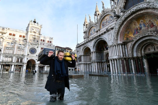 A man carries suitcases as he wades through water during a high tide of 1.44 meters (4.72 feet), in St. Mark's Square, in Venice, Italy, Monday, Dec. 23, 2019.