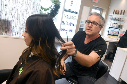 Dmitriy Pomogalov, owner of Aria Salon in Grosse Pointe Woods, works with client Bethany Pejic. Pomogalov spent time in recovery and thanks the Capuchins rehab program called Jefferson House.