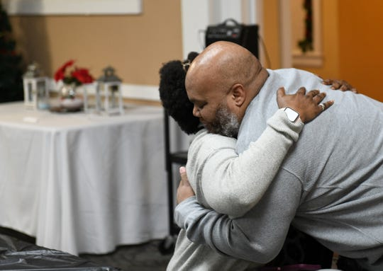 Ray Winans, founder of DLIVE (Detroit Life Is Valuable Everyday) hugs Brenda Hill of Detroit during the service in Detroit. Hill's son was killed in 2009.