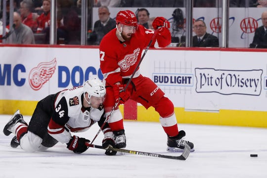 Coyotes center Carl Soderberg (34) and Red Wings defenseman Filip Hronek (17) battle for the puck during the second period on Sunday.