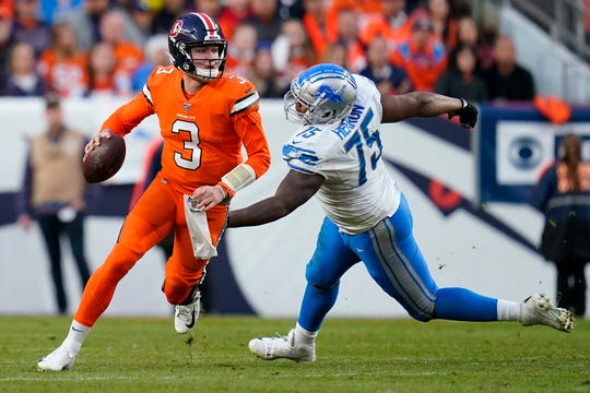 Broncos quarterback Drew Lock (3) eludes Lions defensive end Frank Herron (75) during the second half on Sunday.