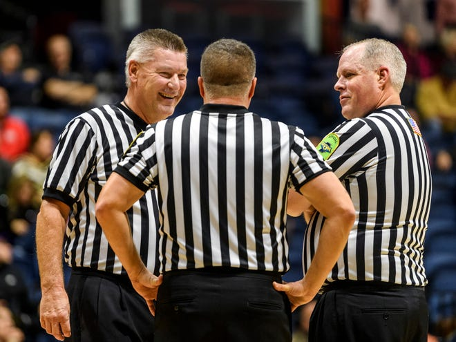 Indiana High School Athletic Association referees discuss the game during a timeout in the fourth quarter of the River City Showcase game between of the Bosse Bulldogs and the Heritage Hills Patriots  at Screaming Eagles Arena in Evansville, Ind., Tuesday, Dec. 10, 2019.